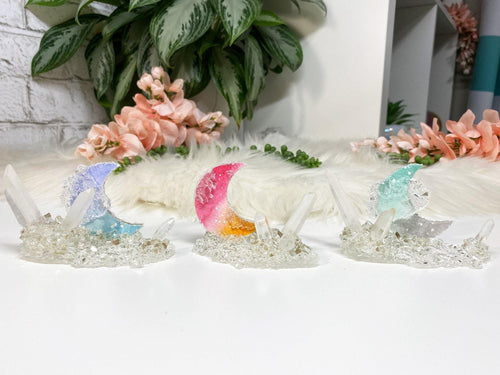 Quartz and resin crystal moon displays are all one of a kind creations.  Each piece features a watercolor moon with a wood backing.  A mixture of natural quartz crystals, glass, and resin combine to create the super sparkly geode look.