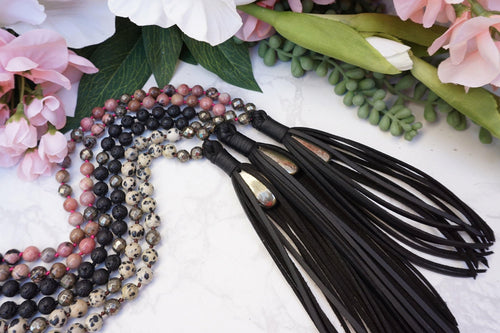 Modern Crystal Mala Necklace featuring natural crysta beads and vegan black faux leather tassels. Pyrite crystal accents that allow you to carry your natural protective crystal energies with style.