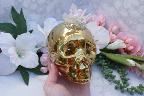 Quartz Skull Piggy Bank. One of a kind with a quartz point cluster on top and a mixture of materials creating a crystal geode pattern on top of a gold ceramic skull piggy bank.