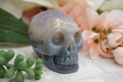 Amethyst Agate Skull. Light and dark coloring with a purple druzy amethyst top. Front view