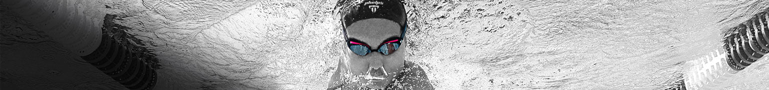 underwater view of four swimmers diving into a pool wearing MP Professional swimming goggles