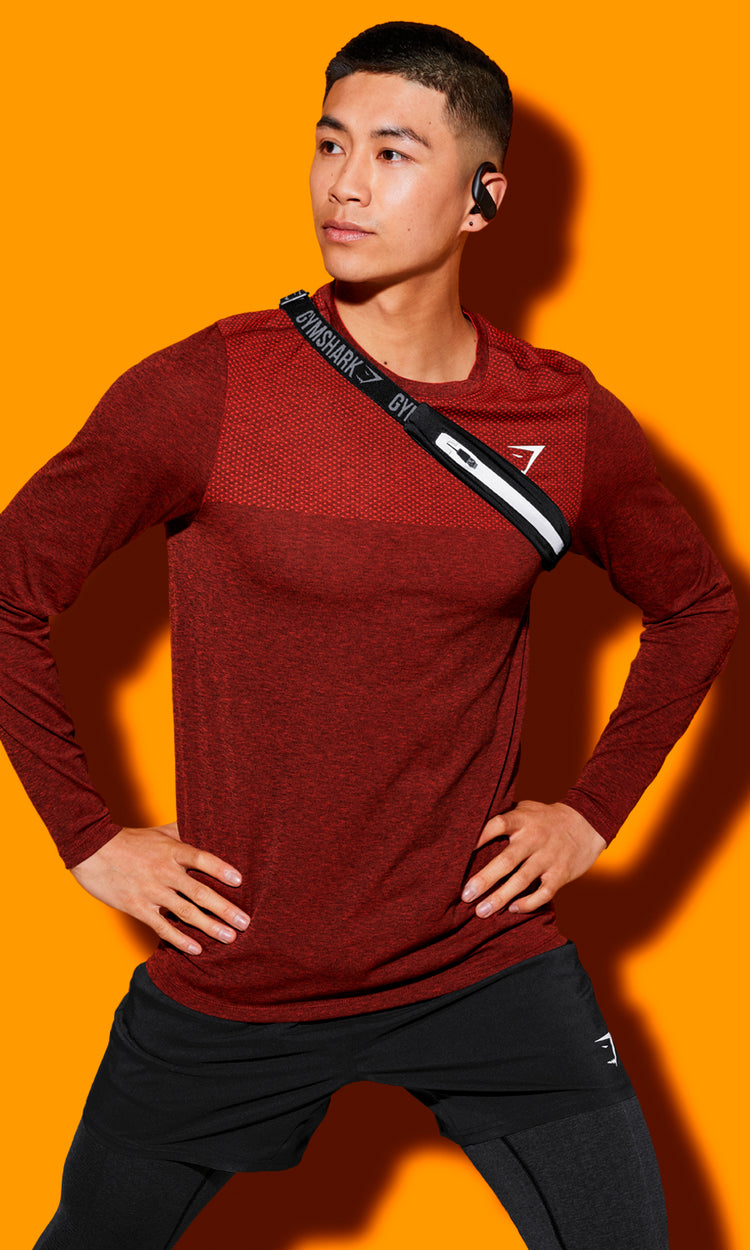Model wearing the Vital seamless long sleeve in red and black Arrival shorts with an orange background.