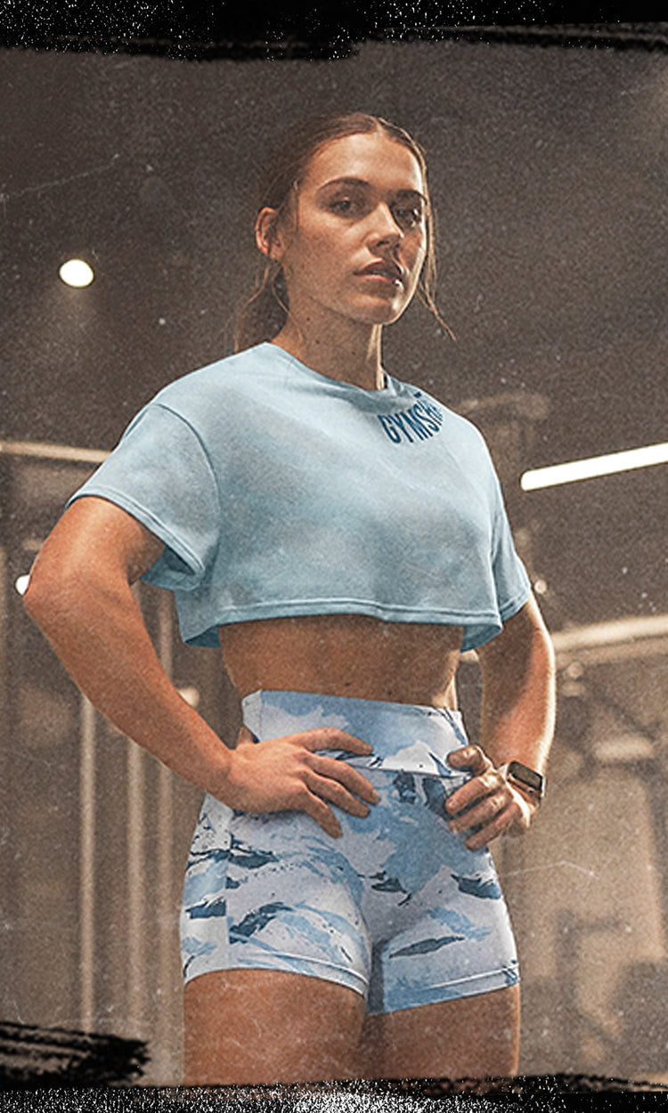 Female Gymshark Athlete posing in a gym in the Power crop top and shorts in light blue print.