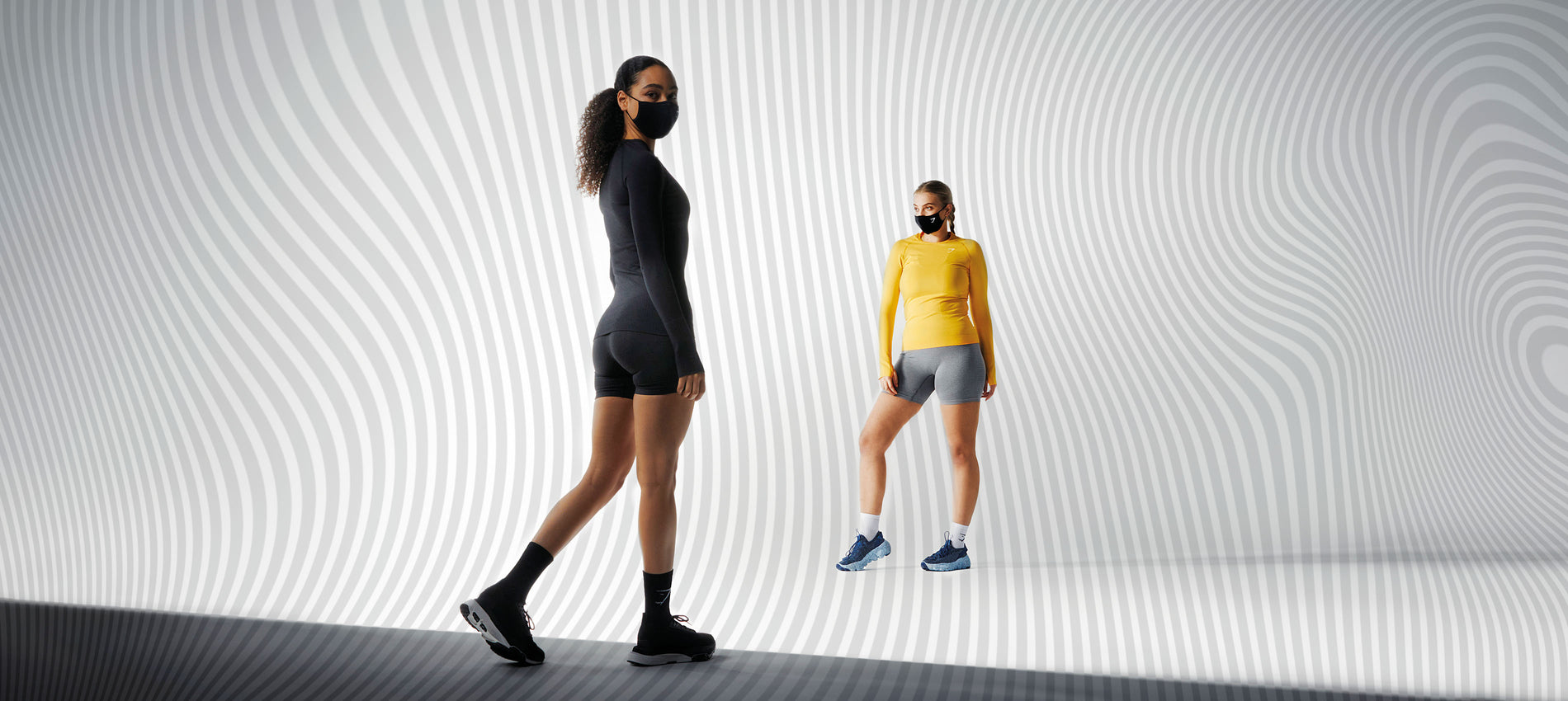 Two female models standing opposite each other wearing Vital Seamless 2.0 and face coverings.