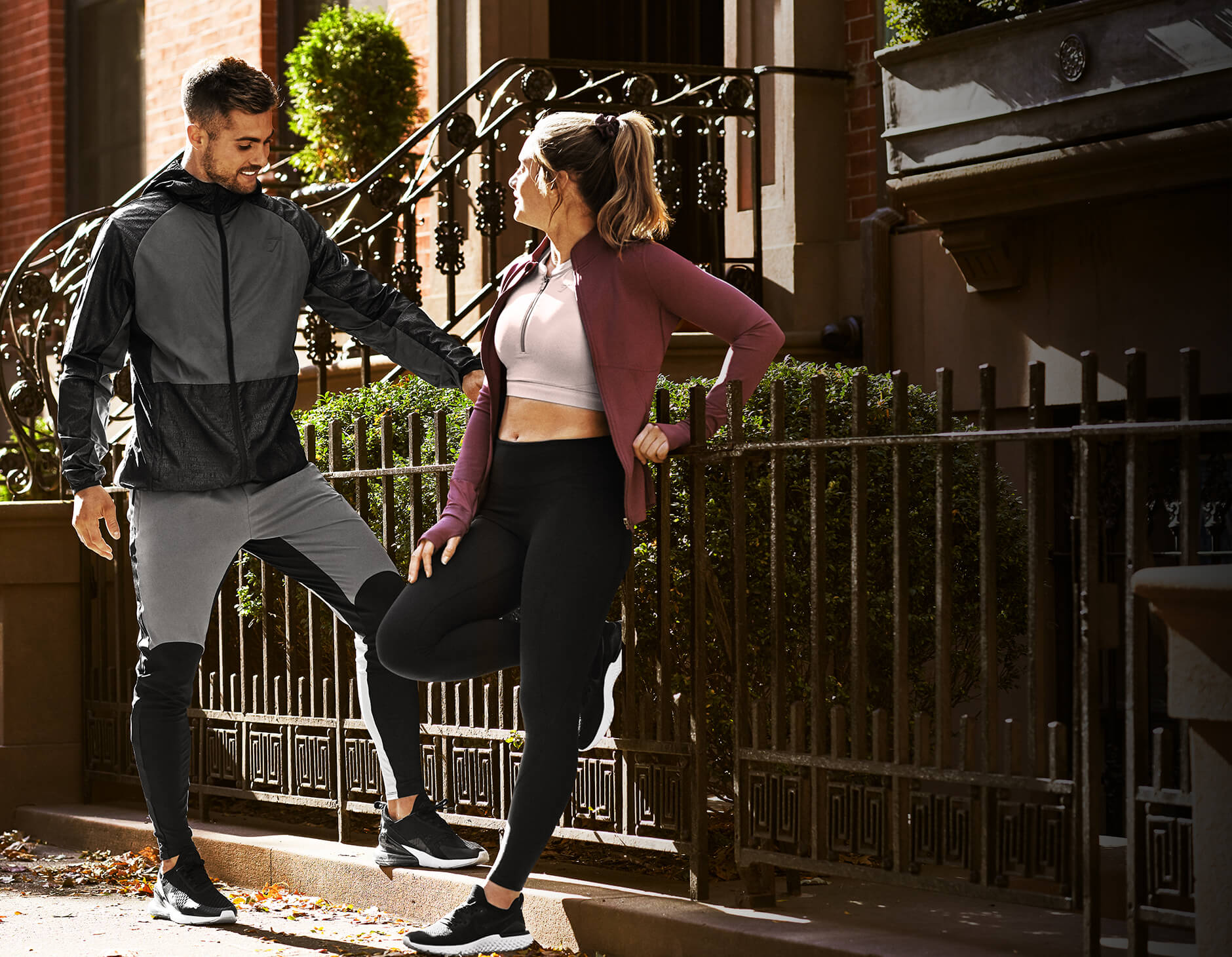 A man and a woman deep in conversation leaning against a metal fence after running wearing Gymshark Speed collection.