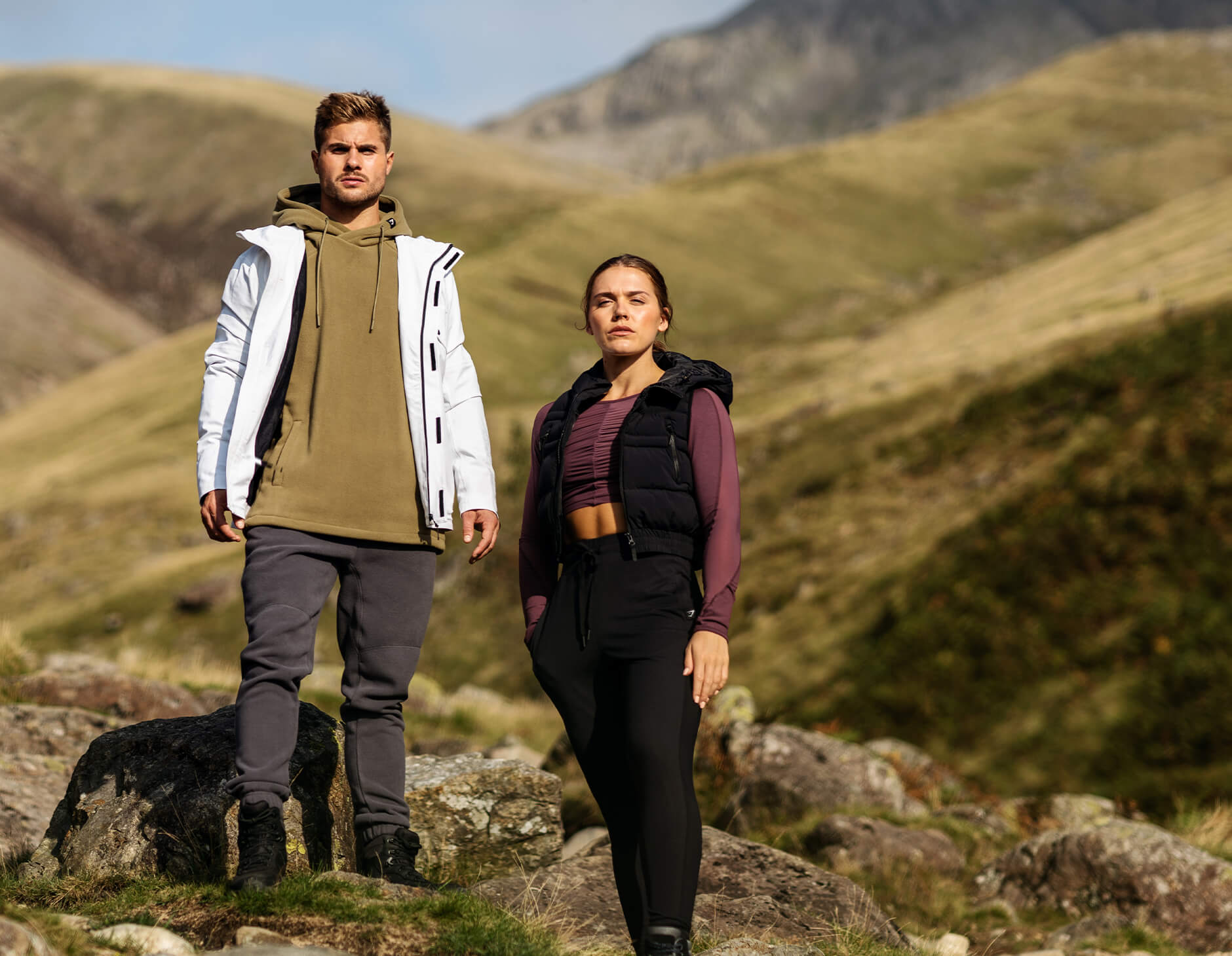 Three Gymshark athletes modelling outerwear in front of a scenic back drop of Lake District. The banner also demonstrates men's and women's layered clothing for cold environment.