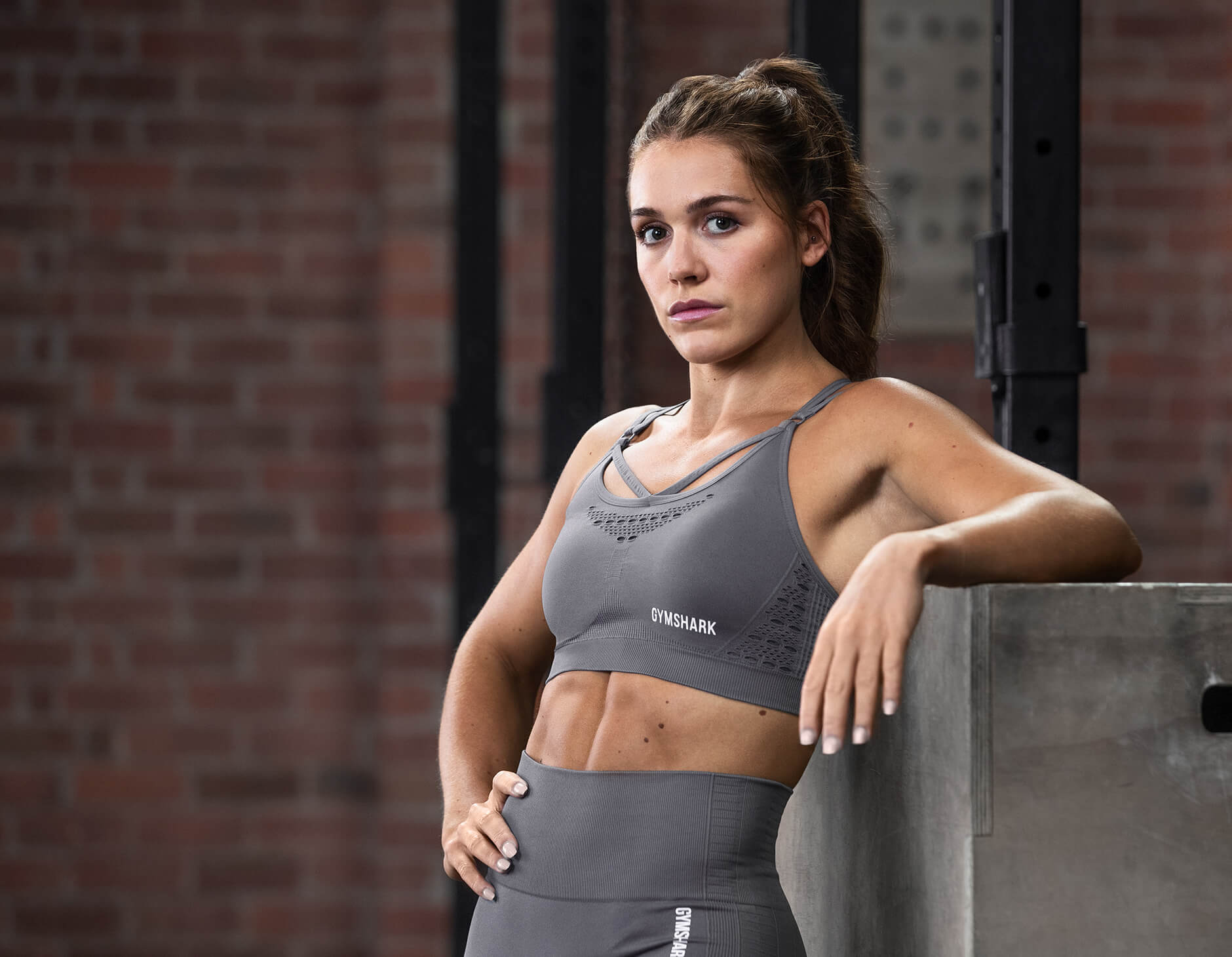 Gymshark athlete modelling Energy Seamless Collection in Grey leaning on a metal box in front of a red brick wall with black pipes.