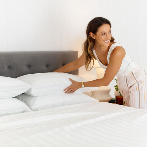 woman putting pillows on a bed with the Breathable Cotton Dream Sheet Set