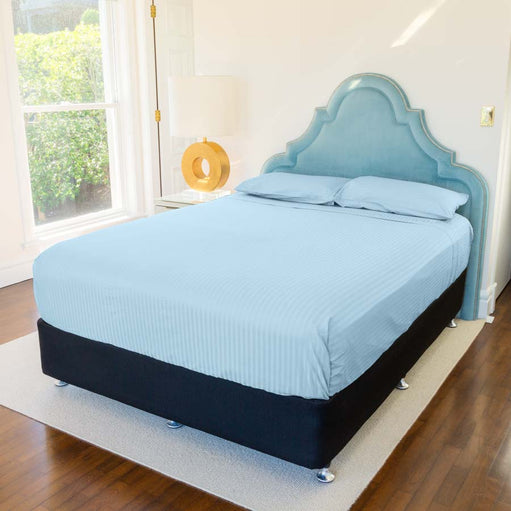 Bed in a bedroom with Light Blue Cotton Sheets