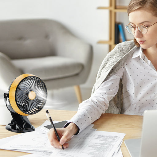 Woman at a desk with an Arctacool Mini Fan next to her