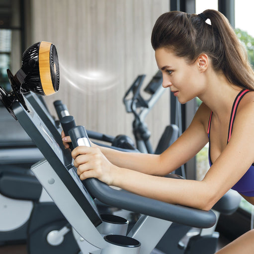 Woman working out with an Arctacool Mini Fan clipped onto the equipment