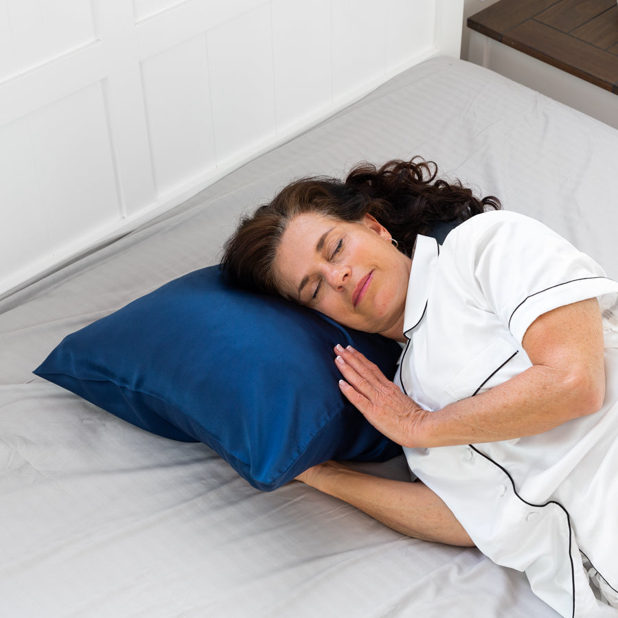 Woman sleeping on a pillow with a Midnight Blue Youth Silk Pillow Case