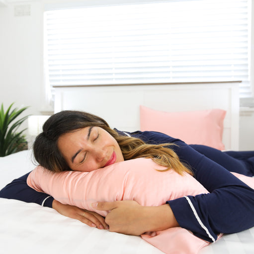 Woman sleeping on a pillow covered with a Rose Gold Youth Silk Pillowcase