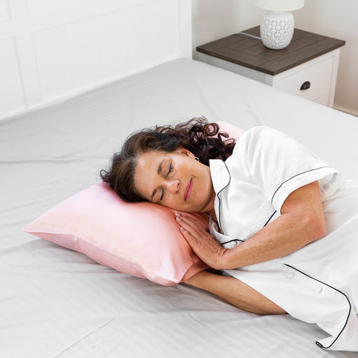 Woman sleeping on a pillow with a Rose Gold Youth Silk Pillowcase