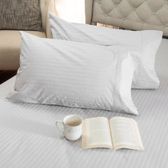 A mug and open book on a bed with 2 pillows and the Silver Cotton Royal Deluxe Dream Sheets