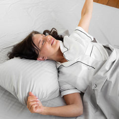 Woman laying and stretching on a bed with the Silver Cotton Royal Deluxe Dream Sheets