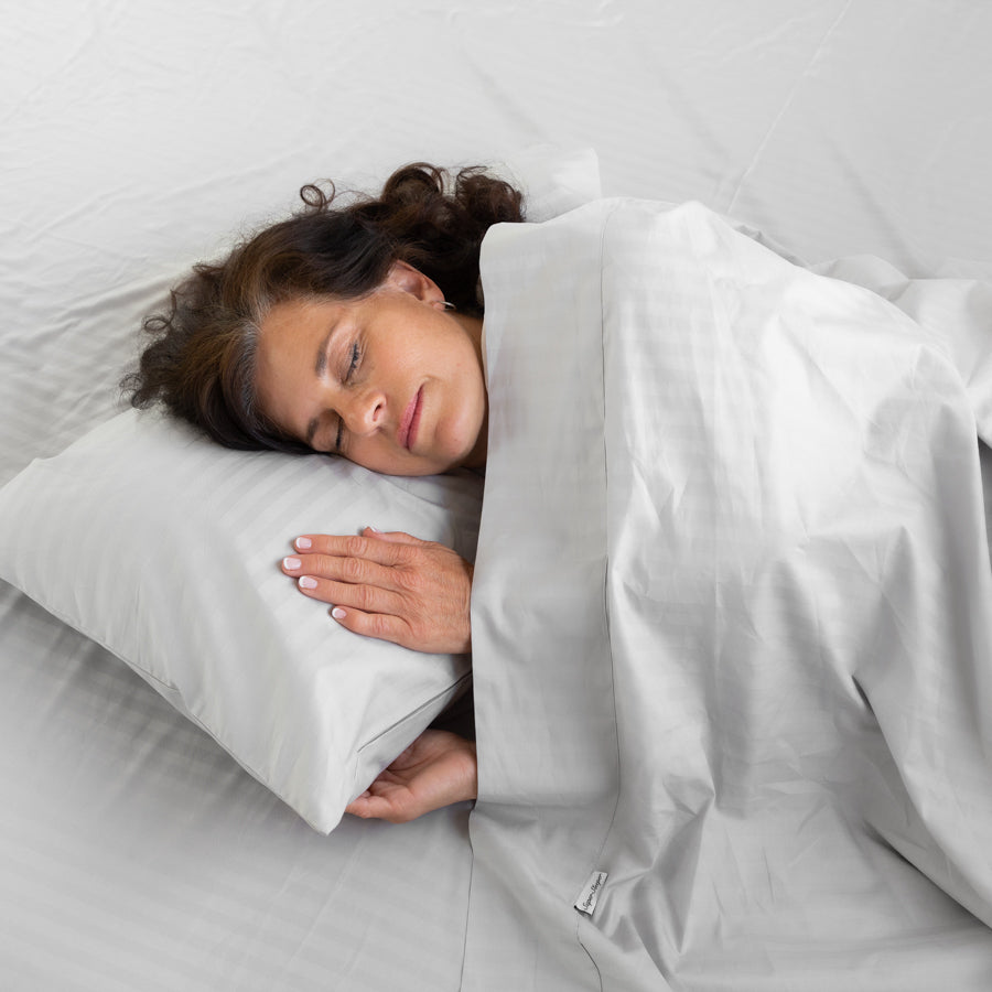 Woman sleeping under the Silver Cotton Royal Deluxe Dream Sheets