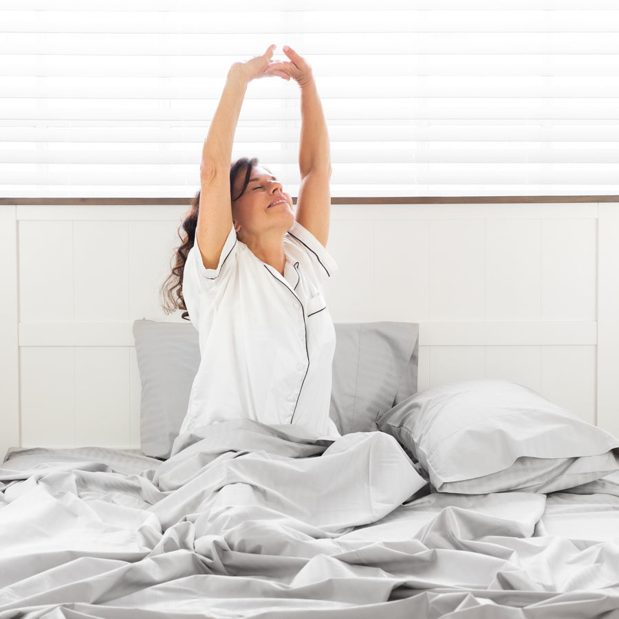 Woman Sitting and stretching on a bed with Silver Cotton Royal Deluxe Dream Sheets