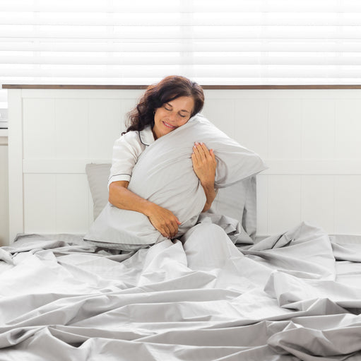 Woman in bed hugging a pillow with the Silver Cotton Royal Deluxe Dream Sheets