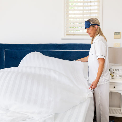 Woman putting Royal Deluxe Breathable Cotton Dream Sheet on a bed to showcase the extra 200cm added to the unique long design