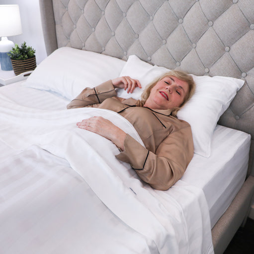 Woman sleeping in a bed with the Royal Deluxe Super Weave Dream Sheet