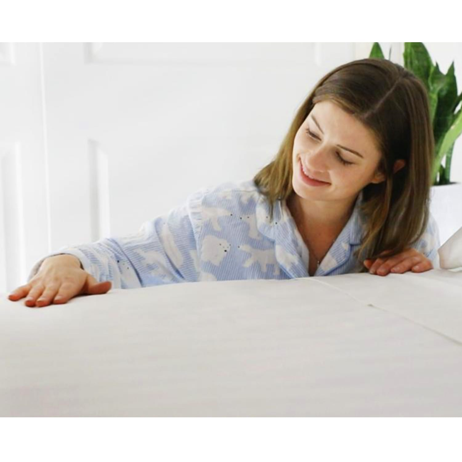 Woman touching Royal Deluxe Super Weave Dream Sheet on a bed
