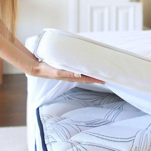 Mattress topper being laid on a bed