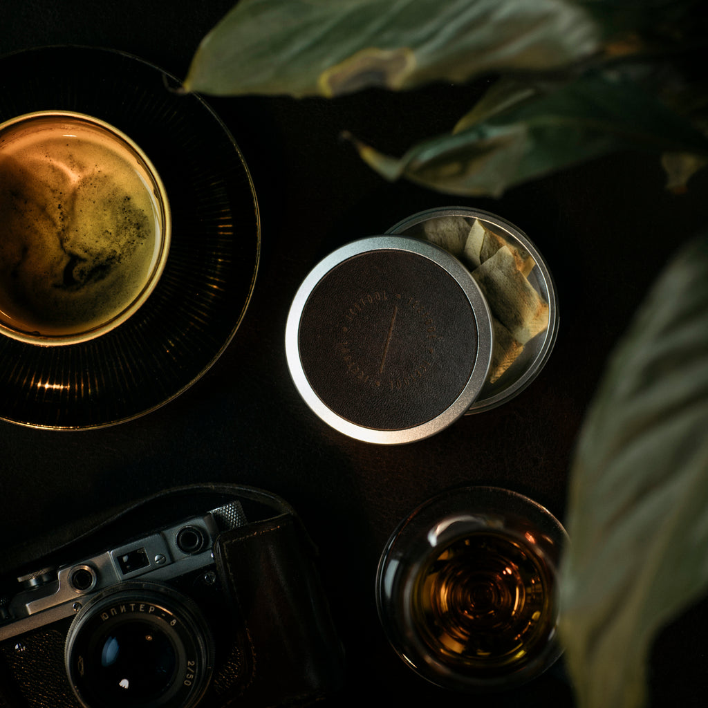 Icetool Slim Can Leatheface for portion snus and nicotine pouches - Silver aluminum with a custom made havana leather covered lid. Photo on black table with a cup of coffee, a vintage camera and a glass of cognac.