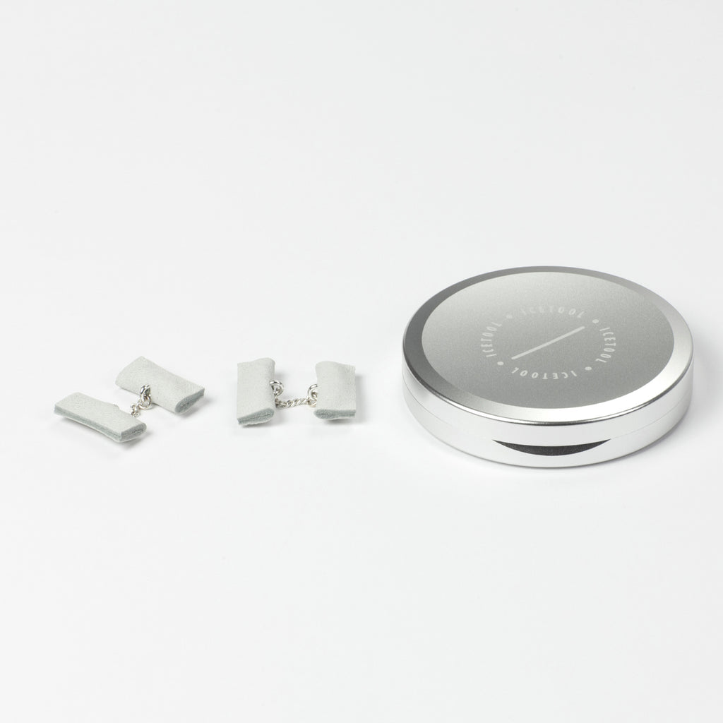 Icetool Slim Can for portion snus and nicotine pouches - Silver color anodised aluminum. On a white table with a pair of white gTie cufflinks.