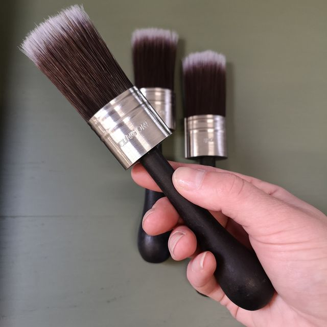 Hand holding Cling On! brushes