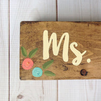 hand painted wood sign with teal and coral flowers