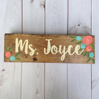 hand painted stained wooden sign with teal and coral flowers