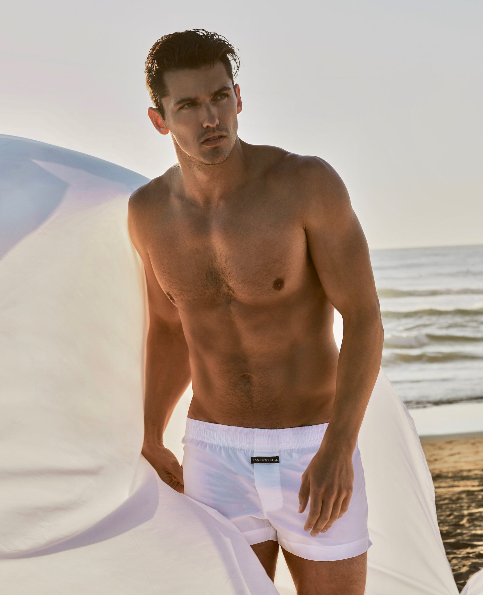 Model Taylor Miller wearing BANG&STRIKE Hard Times Woven Boxer on a beach in LA