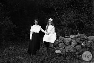 Two Young Women Posing Besides Stone Wall Together Outside Forest, Early 1900s