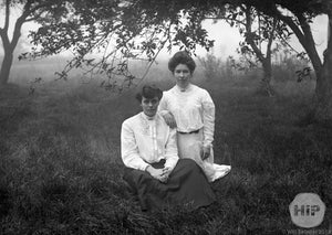 Two Young Women Sitting Besides Each Other in Misty Overgrown Field of Grass, Early 1900s