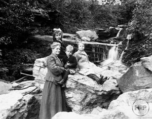 Middle-Aged Woman and Three Angelic Young Children Posing by Calming Creekside