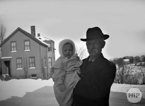 Elderly Elegant Man Posing with Cherubic Young Child on a Snowy Winter Afternoon