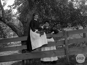 Lovely Young Women Holding Herbs and Posing in Front of Wooden Fence and Tree, Early 1900s
