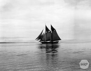 Double-Masted Schooner with Dark Sails Travelling through the Calm, Foggy Waters of MA