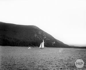 View of Sailboats Positioned in Front of a Large, Magnificent Hill Covered with Trees in MA
