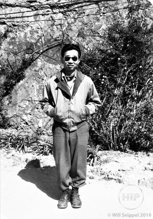 George Sakata in Sunglasses and Casual Wear Smiling and Posing in Front of Woodland Area