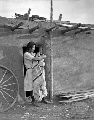Native American woman with Child  in Adobe Doorway