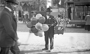 Balloon Vendor in the Streets at Unidentified Circus or Carnival