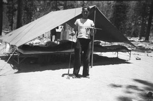 Photograph of Youth Displaying a Proud Catch of Fingerling Fish in Front of Campsite about 1950