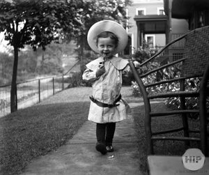 Child Smoking a Pipe in the front yard with a hat
