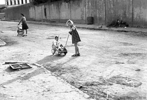 Little Girl Around 6 Years Old Playing in Street with Baby Sibling in WWII Italy