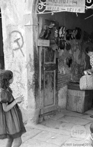 Little Girl Around 8 Years Old Standing in Entryway of Italian Shoe Shop with Communism Symbol on its Outer Wall, WWII