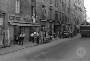 Man Sets Up Shop on Narrow, Bustling Street Beside Apartment Buildings and Pedestrians, Italy 1940s