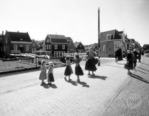 Young Girls in Traditional Dress-Wear Conversing Together on the Streets of a Quaint Dutch Village in Holland