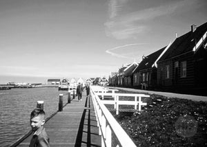 Pedestrians Walking on the Docks of a Lovely Cabin-Lined Harbor in Holland